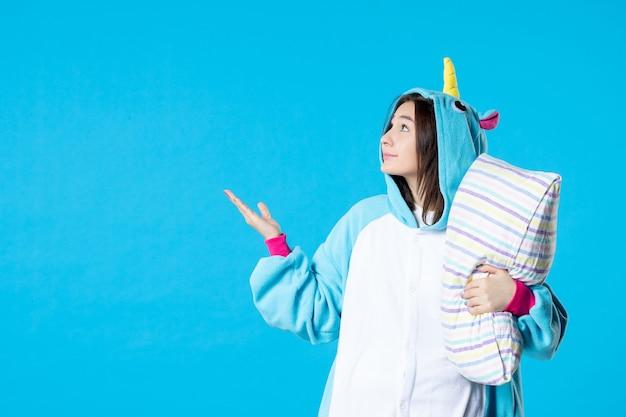 Vooraanzicht jonge vrouw in kigurumi voor pyjama party knuffelen kussen op blauwe achtergrond cartoon droom anime slaap laat vrienden bed spel plezier kleur