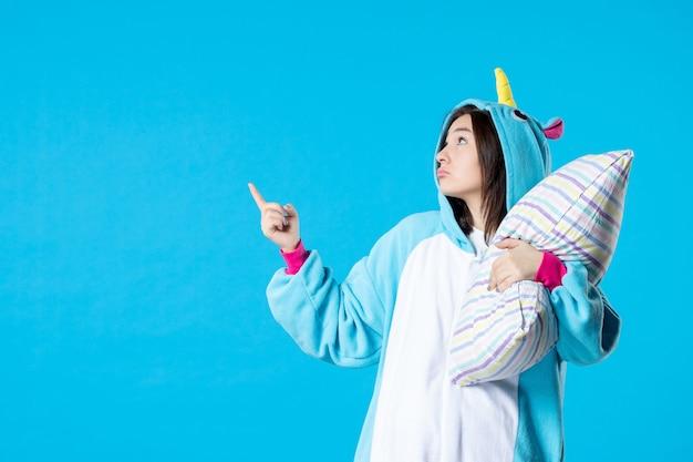 Vooraanzicht jonge vrouw in kigurumi voor pyjama party knuffelen kussen op blauwe achtergrond cartoon droom anime slaap laat vrienden spel nacht plezier kleur