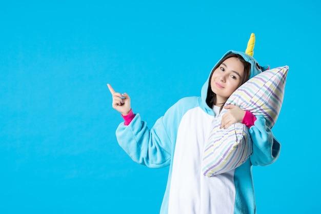 Vooraanzicht jonge vrouw in kigurumi voor pyjama party knuffelen kussen op blauwe achtergrond cartoon droom anime slaap vrienden bed spel nacht plezier kleur