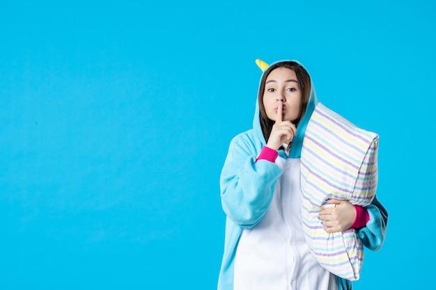 Vooraanzicht jonge vrouw in kigurumi voor pyjama party knuffelen kussen op blauwe achtergrond cartoon droom slaap vrienden bed spel nacht plezier anime laat