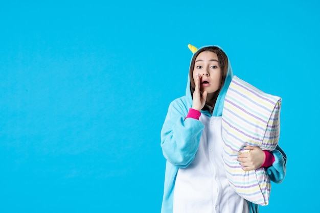 Vooraanzicht jonge vrouw in kigurumi voor pyjama party knuffelen kussen op blauwe achtergrond cartoon droom slaap vrienden bed spel nacht plezier kleur anime laat fluisteren