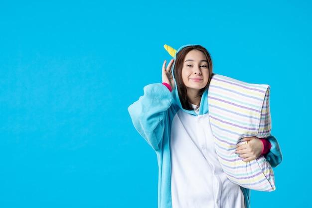 Vooraanzicht jonge vrouw in kigurumi voor pyjama party knuffelen kussen op blauwe achtergrond cartoon droom slaap vrienden bed spel nacht plezier kleur anime laat glimlach