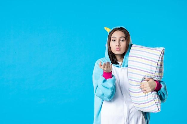 Vooraanzicht jonge vrouw in kigurumi voor pyjama party knuffelen kussen op blauwe achtergrond cartoon droom slaap vrienden bed spel nacht plezier kleur anime laat kus