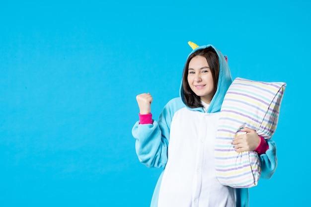 Vooraanzicht jonge vrouw in kigurumi voor pyjama party knuffelen kussen op blauwe achtergrond cartoon droom slaap vrienden bed spel nacht plezier kleur anime laat