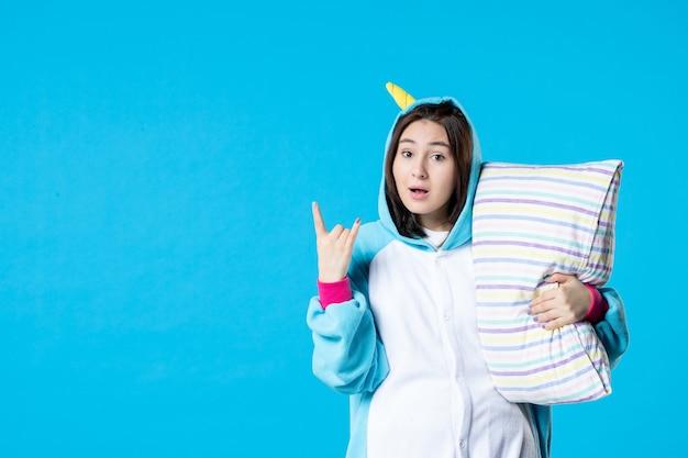 Vooraanzicht jonge vrouw in kigurumi voor pyjama party knuffelen kussen op blauwe achtergrond cartoon droom slaap vrienden bed spel plezier kleur anime laat