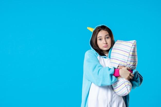 Vooraanzicht jonge vrouw in kigurumi voor pyjama party knuffelen kussen op blauwe achtergrond cartoon droom slaap vrienden nacht plezier kleur anime laat bed