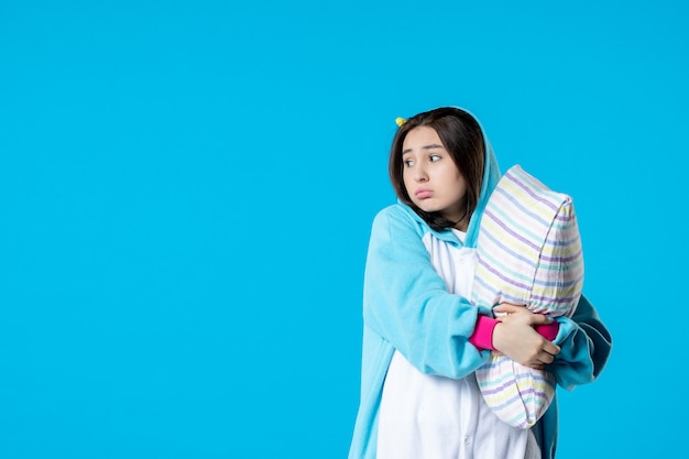 Vooraanzicht jonge vrouw in kigurumi voor pyjama party knuffelen kussen op blauwe achtergrond cartoon droom slaap vrienden spel nacht kleur anime laat bed