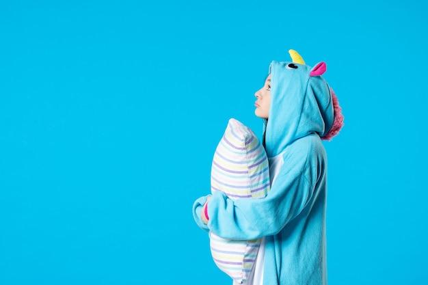 Vooraanzicht jonge vrouw in kigurumi voor pyjama party knuffelen kussen op blauwe achtergrond cartoon droom slaap vrienden spel nacht plezier kleur anime bed