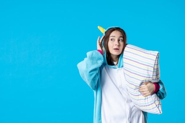 Vooraanzicht jonge vrouw in kigurumi voor pyjama party knuffelen kussen op blauwe achtergrond cartoon droom slaap vrienden spel nacht plezier kleur anime laat bed