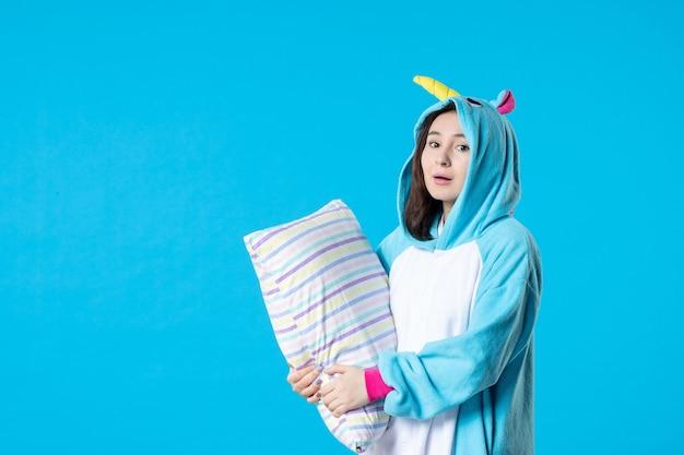 Vooraanzicht jonge vrouw in kigurumi voor pyjama party knuffelen kussen op blauwe achtergrond cartoon droom slaap vrienden spel nacht plezier kleur laat bed