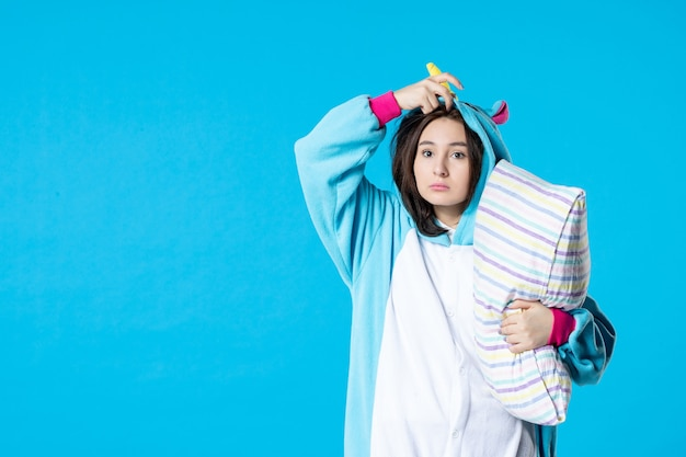 Vooraanzicht jonge vrouw in kigurumi voor pyjama party knuffelen kussen op blauwe achtergrond cartoon droom slaap vrienden spel nacht plezier kleuren anime laat bed
