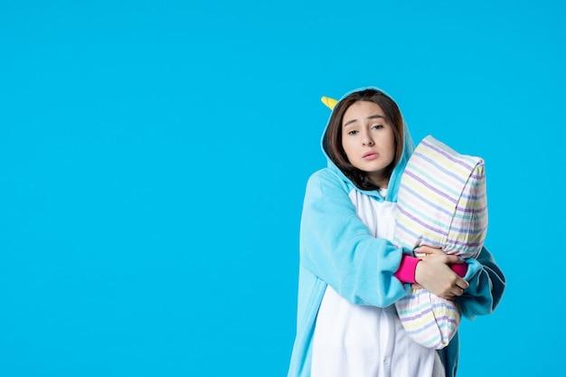 Vooraanzicht jonge vrouw in kigurumi voor pyjama party knuffelen kussen op blauwe achtergrond cartoon droom slaap vrienden spel plezier kleur anime laat bed