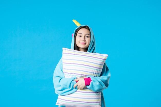 Vooraanzicht jonge vrouw in kigurumi voor pyjama party met kussen op blauwe achtergrond cartoon droom slaap vrienden nacht plezier kleur anime laat bed