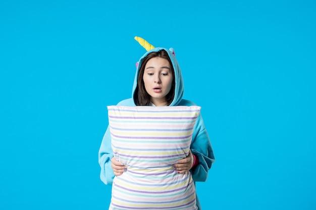 Vooraanzicht jonge vrouw in kigurumi voor pyjama party met kussen op blauwe achtergrond cartoon droom slaap vrienden spel nacht plezier anime laat bed