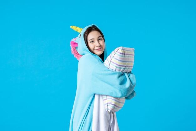 Vooraanzicht jonge vrouw in kigurumi voor pyjama party met kussen op blauwe achtergrond cartoon droom slaap vrienden spel nacht plezier kleur anime laat bed glimlach