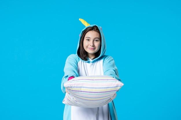 Vooraanzicht jonge vrouw in kigurumi voor pyjama party met kussen op blauwe achtergrond cartoon droom slaap vrienden spel nacht plezier kleur laat bed