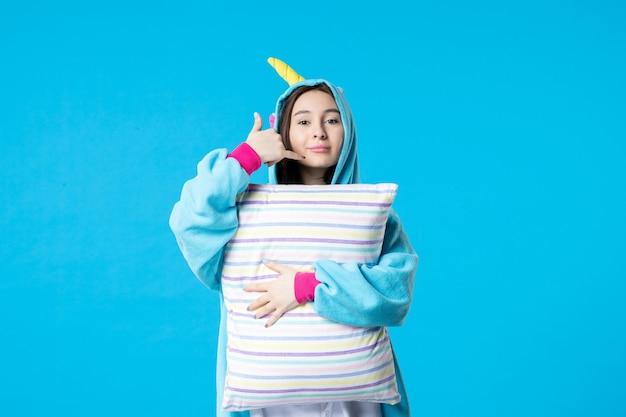 Vooraanzicht jonge vrouw in kigurumi voor pyjamafeest met kussen op een lichtblauwe achtergrond cartoon game droom slaap vrienden nacht plezier kleuren anime laat bed