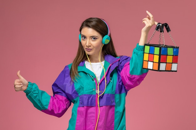 Vooraanzicht jonge vrouw in kleurrijke moderne jas oortelefoons met tas op de roze muur, kleurenfoto vrouw mode kleding