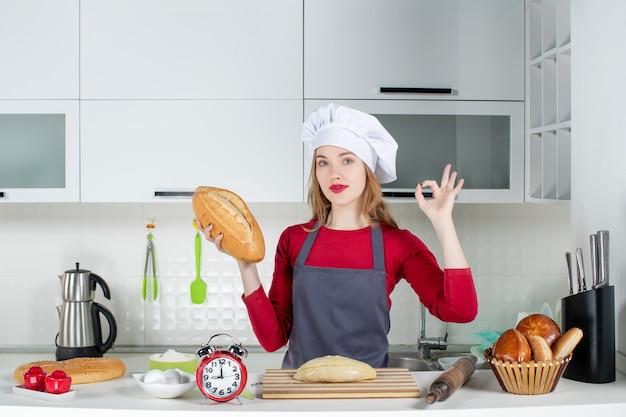 Vooraanzicht jonge vrouw in koksmuts en schort die brood vasthoudt om okey teken in de keuken te maken