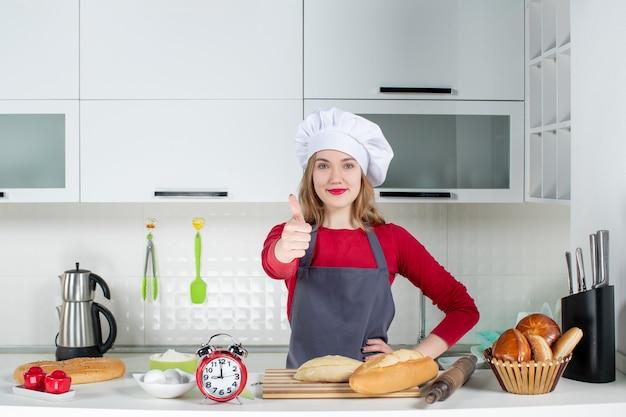 Vooraanzicht jonge vrouw in koksmuts en schort die duim omhoog tekent in de keuken