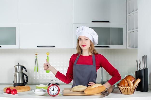 Vooraanzicht jonge vrouw in koksmuts en schort die duimen opgeeft in de keuken