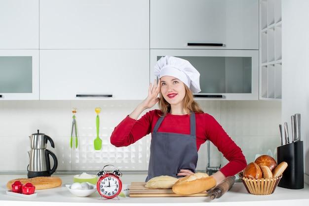Vooraanzicht jonge vrouw in koksmuts en schort die iets in de keuken denkt