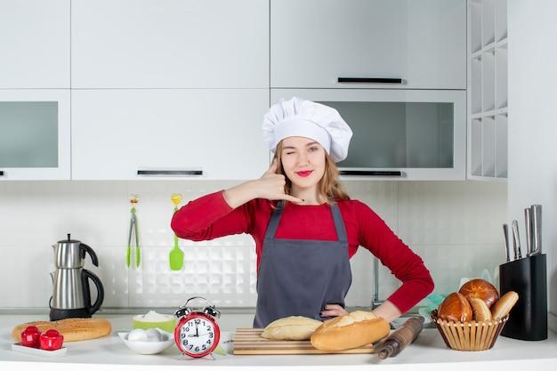 Vooraanzicht jonge vrouw in koksmuts en schort die me een telefoongebaar maakt in de keuken