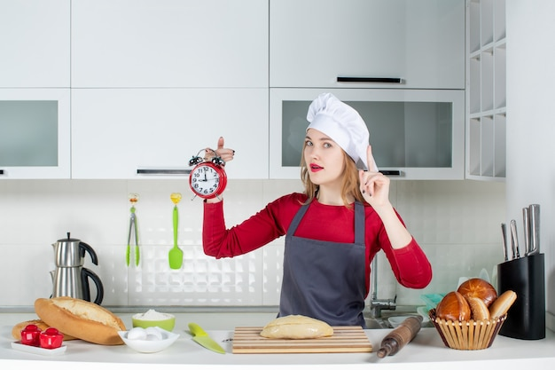 Vooraanzicht jonge vrouw in koksmuts en schort met rode wekker die verrast met een idee in de keuken
