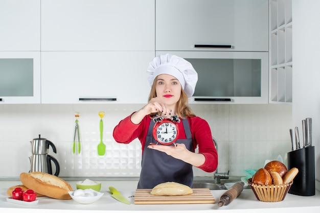 Vooraanzicht jonge vrouw in koksmuts en schort met rode wekker in de keuken