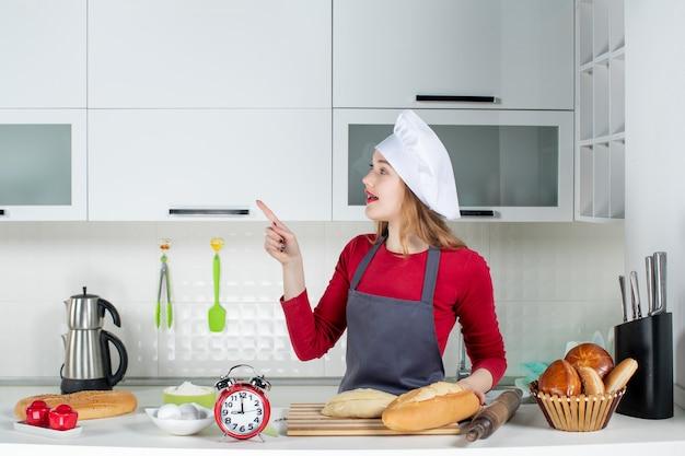 Vooraanzicht jonge vrouw in koksmuts en schort wijzend naar links in de keuken