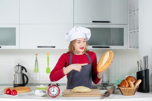 Vooraanzicht jonge vrouw in koksmuts en schort wijzend op brood in de keuken