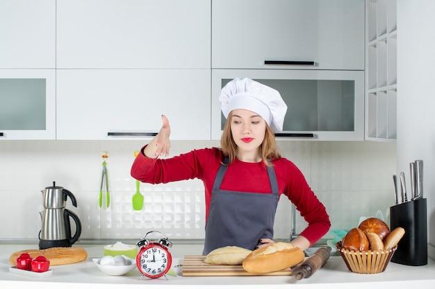 Vooraanzicht jonge vrouw in koksmuts en schort wijzend op rode wekker in de keuken