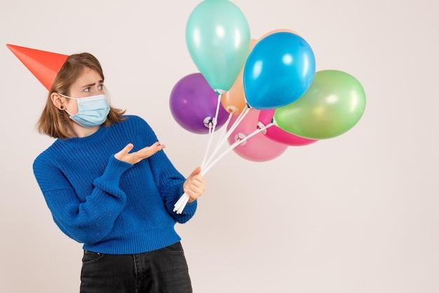 Vooraanzicht jonge vrouw in masker met kleurrijke ballonnen