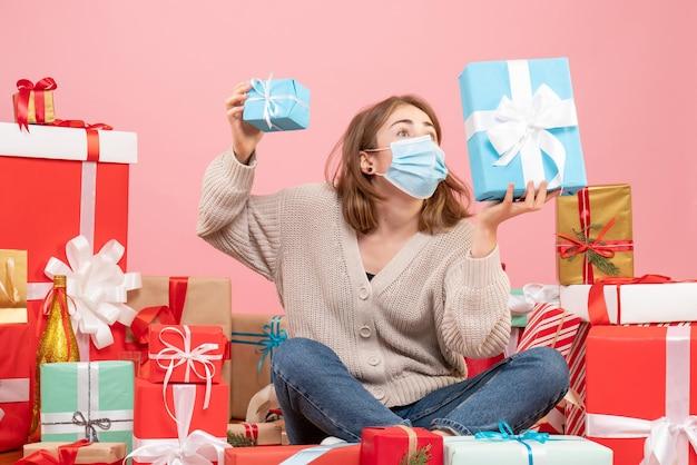 Vooraanzicht jonge vrouw in masker rond kerstcadeautjes zitten