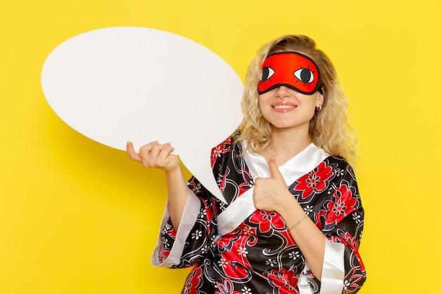 Vooraanzicht jonge vrouw in nacht gewaad met enorme witte bord glimlachend op lichtgele muur slaap nacht bed model meisje kleur