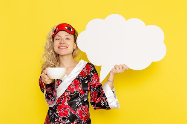 Vooraanzicht jonge vrouw in nacht gewaad met groot wit bord en koffie drinken op gele bureau slaap nacht bed model kleur