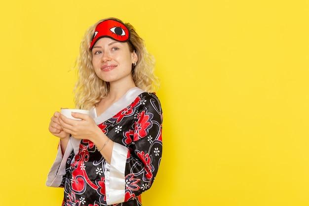 Vooraanzicht jonge vrouw in nachtjas en het dragen van een oogmasker voorbereiden om te slapen koffie drinken op lichtgele muur slaap vrouwelijk model nachtbed
