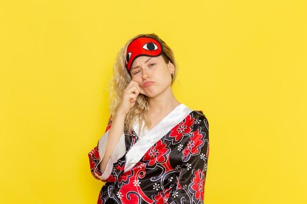 Vooraanzicht jonge vrouw in nachtjas en het dragen van een oogmasker voorbereiden om te slapen moe poseren op lichtgele muur slaap vrouwelijk model nachtbed