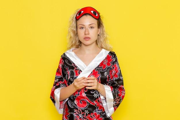 Vooraanzicht jonge vrouw in nachtjas en het dragen van een oogmasker voorbereiden om te slapen op de lichtgele muur nacht slaap vrouwelijke donkere kleur