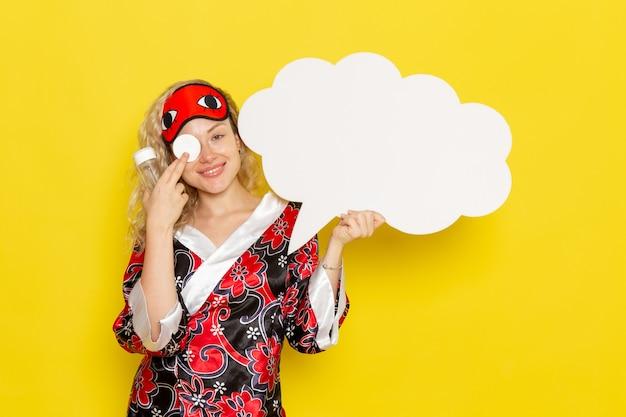 Vooraanzicht jonge vrouw in nachtjas oogmasker met groot wit bord en kolven glimlachend op gele muur slaap nacht bed model kleur