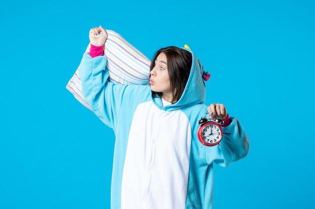 Vooraanzicht jonge vrouw in pyjamafeest met klokken en kussen op blauwe achtergrond bed droom slaap laat rusten nachtmerrie nacht vrienden