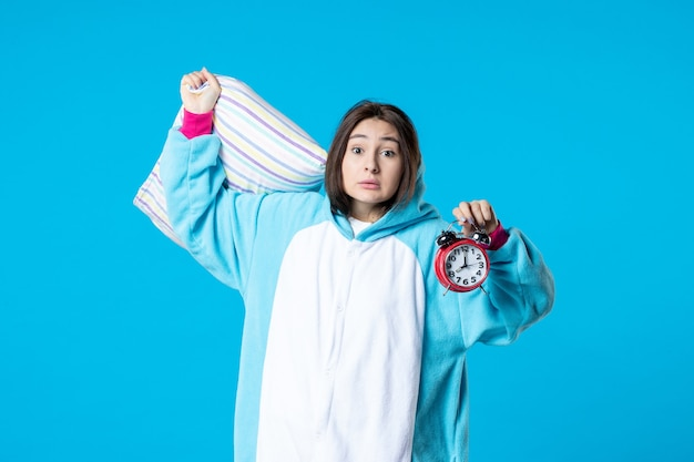 Vooraanzicht jonge vrouw in pyjamafeest met klokken en kussen op blauwe achtergrond nachtmerrie bed droom slaap laat rusten nacht vrienden leuke kleur