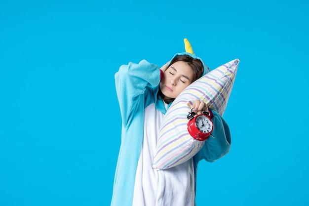 Vooraanzicht jonge vrouw in pyjamafeest met klokken kussen en wakker worden op blauwe achtergrond bed droom slaap laat rusten nacht vrienden geeuwen