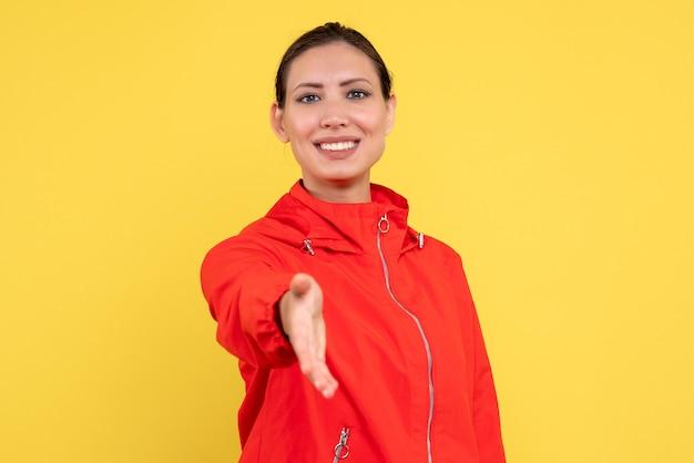 Vooraanzicht jonge vrouw in rode jas handen schudden op gele achtergrond