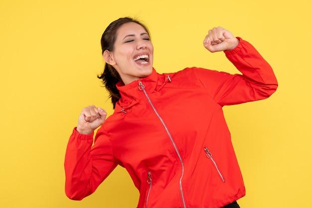 Vooraanzicht jonge vrouw in rode jas vreugde op gele achtergrond