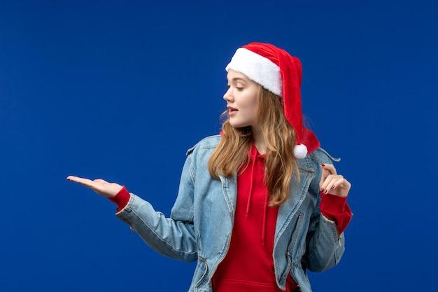 Vooraanzicht jonge vrouw in rode kerst pet op de blauwe achtergrond kerst emotie kleur
