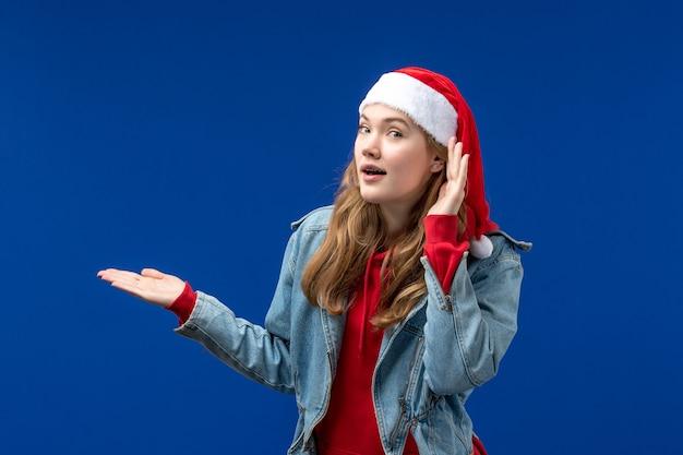 Vooraanzicht jonge vrouw in rode kerst pet op een blauwe achtergrond kerst emoties kleur