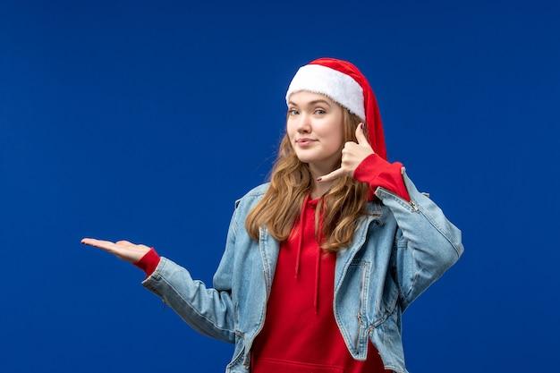 Vooraanzicht jonge vrouw in rode kerst pet op lichtblauwe achtergrond kerst emotie kleur