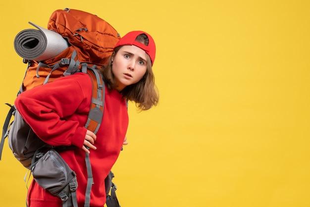 Vooraanzicht jonge vrouw in rode rugzak staande op gele muur