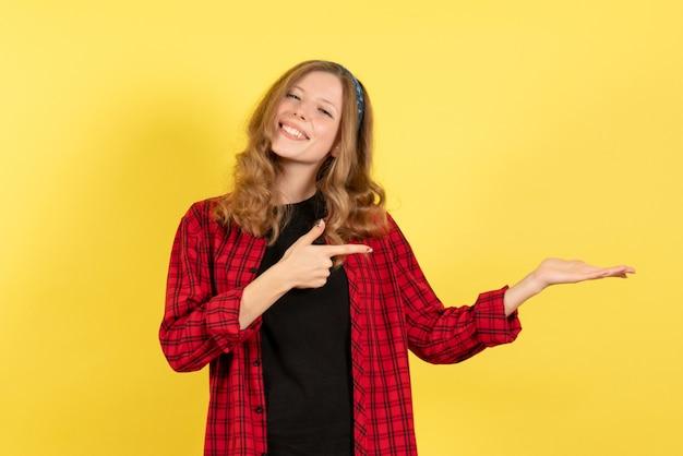 Vooraanzicht jonge vrouw in rood geruit overhemd glimlachend en poseren op gele achtergrond meisjes vrouw emoties model kleur mens